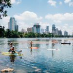 Stand up paddle board yoga with city views behind