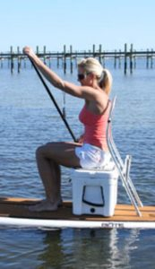 a lady sitting on a hard-sided cooler while paddle boarding